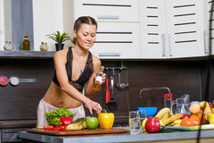 Portrait of a young slim woman in lingerie in the kitchen Stock Images