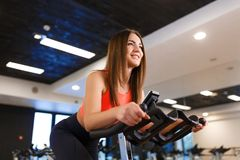 Portrait of young slim woman in sportwear workout on exercise bike in gym. Sport and wellness lifestyle concept stock images