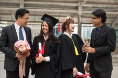 Graduate women students with family. Portrait of Young smile female students in black graduation gowns happy with fathers. Portrait with delight and graceful Stock Photography