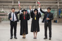 Happy gaduated female student with family. Portrait of Young smile female students in black graduation gowns happy with fathers. Two family raise hands with Stock Photos