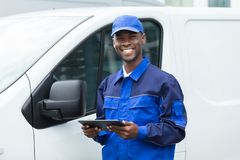 Young African Delivery Man Holding Digital Tablet royalty free stock photo
