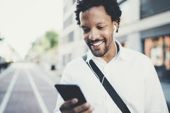 Portrait of young smiling african man using smartphone hands while standing at sunny city street.Concept of happy Stock Image