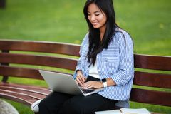 Portrait of a young smiling asian female student working. On laptop computer while sitting on the bench at the park Stock Photos