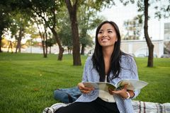Portrait of young smiling asian woman with book sitting in park, Stock Photography