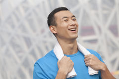 Portrait of young smiling athletic man in a blue t-shirt outdoors with towel around neck Stock Photos