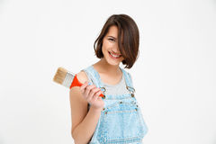 Portrait of young smiling beautiful girl, holding paint brush Stock Image