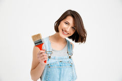 Portrait of young smiling beautiful girl, holding paint brush Royalty Free Stock Photography