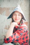 Portrait of young beautiful woman in newspaper hat. Repair home concept. Stock Images