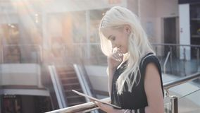 Portrait of young smiling blonde teenager girl inside shopping gallery mall Royalty Free Stock Image