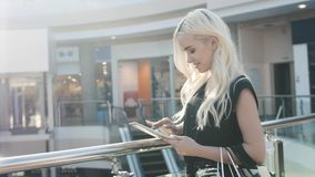 Portrait of young smiling blonde teenager girl inside shopping gallery mall Stock Photos