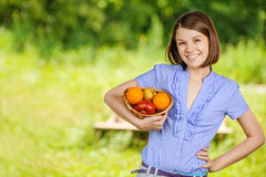 Portrait of young smiling brunette holding basket with fruits Royalty Free Stock Photo