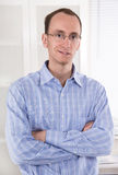Portrait of a young smiling business man in blue shirt. Portrait of a young smiling business man in blue Shirt with folded arms Stock Photo