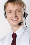 Portrait of young smiling business man with headset on white Royalty Free Stock Photography
