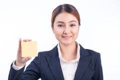 A portrait of a young smiling business woman showing blank stick Royalty Free Stock Images