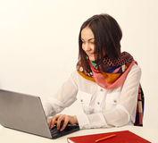 Portrait of a young smiling business woman using laptop at offic Royalty Free Stock Photo
