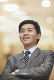 Portrait of young smiling businessman with arms crossed looking away, focus on foreground Stock Photos
