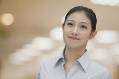Portrait of young smiling businesswoman in a button down shirt, indoors, focus on foreground Stock Photos