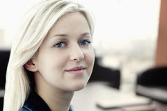Portrait of young smiling businesswoman with coworkers in the background Stock Image