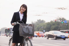 Portrait of young smiling businesswoman riding a bicycle on the street in Beijing, looking at camera Stock Photo