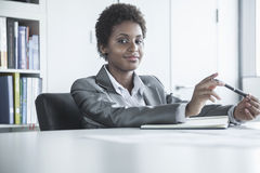 Portrait of young smiling businesswoman sitting at a table and holding a pen, looking at camera Royalty Free Stock Photography