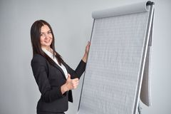 Portrait of young smiling businesswoman standing by flipchart in office royalty free stock photo