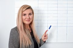 Portrait of young smiling businesswoman standing near flipchart in office and pointing on it stock image