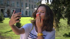 Portrait of a young smiling caucasian girl standing in the park and using a smartphone, making selfie, university in the stock video footage