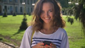 Portrait of a young smiling caucasian girl standing in the park and using a smartphone university in the background stock video