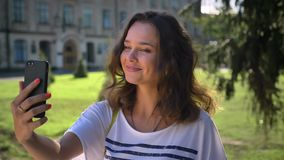 Portrait of a young smiling caucasian girl standing in the park and using smartphone saying hello to video chat, making stock footage