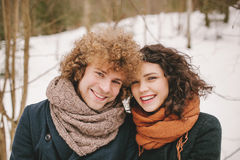 Portrait of young smiling couple with curly hair in winter fores Royalty Free Stock Photos