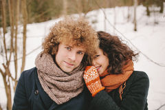Portrait of young smiling couple with curly hair in winter fores Royalty Free Stock Images