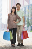 Portrait of young, smiling couple going shopping and holding colorful shopping bags in the street, looking at camera, Beijing, Chi Stock Images