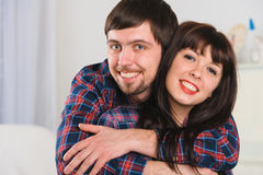 Portrait of young smiling couple at home interior Stock Photos
