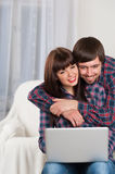 Portrait of young smiling couple using laptop while sitting on c Royalty Free Stock Photography
