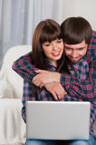 Portrait of young smiling couple using laptop while sitting at h Stock Photo