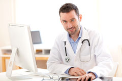 Portrait of a young smiling doctor in his office Royalty Free Stock Image