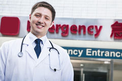 Portrait of young smiling doctor outside of the hospital, emergency room sign in the background stock images