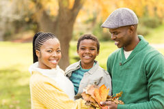 Portrait of a young smiling family holding leaves Royalty Free Stock Photo