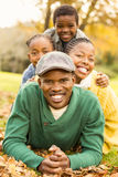 Portrait of a young smiling family lying in leaves. On an autumns day stock image