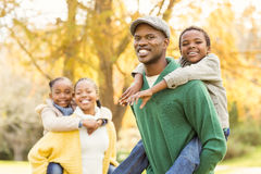 Portrait of a young smiling family in piggyback. On an autumns day stock photos