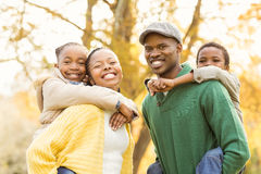 Portrait of a young smiling family in piggyback. On an autumns day royalty free stock image