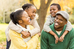 Portrait of a young smiling family in piggyback. On an autumns day stock image