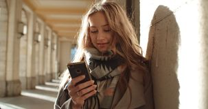 Attractive brunette young woman using phone in a city. royalty free stock images