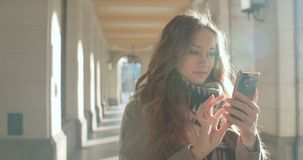 Attractive brunette young woman texting on phone in a city. Portrait of young smiling fashion girl standing with smartphone stock video