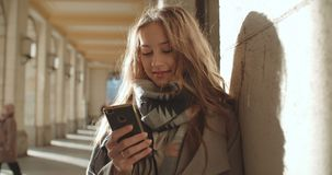 Attractive brunette young woman using phone in a city. Portrait of young smiling fashion girl standing with smartphone stock video footage