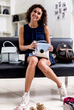 Portrait of young smiling female shopper sitting with a new handbag on her laps in accessories shop.  Stock Images