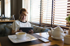 Portrait of young smiling female using touch pad in headphones while calling on video to her boyfriend Royalty Free Stock Photography