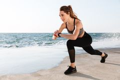 Portrait of young smiling  fitness woman checking time while doi. Ng fitness exercise for legs, seaside outdoor Royalty Free Stock Image