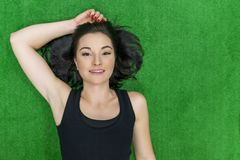 Portrait of young smiling fitness woman laying on floor in gym. Top view, brunette woman on green surface, copy space. Beauty, royalty free stock photos