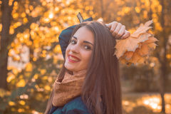 Portrait of a young smiling girl in autumn Park with leaves in hand, close-up. Portrait of a young smiling girl in autumn Park with leaves in hand Stock Images